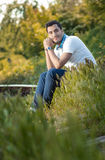 Man sitting on grass in forest Royalty Free Stock Photography