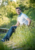 Man sitting on grass in forest Stock Images