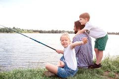 Man is sitting on grass and holding fish-rod. He is trying to catch some fish. Boy is standing behind and hugging him. Girl is looking behind and waving on stock photo