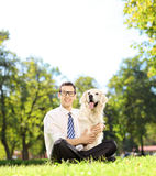 Man sitting on a grass and hugging his labrador retriever dog in Stock Images