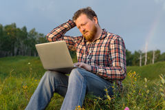 Man sitting on the grass with a laptop on his knees. Stock Photography