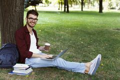 Man sitting on grass with laptop outdoors. Casual man in glasses sitting on grass focused on working on laptop with straight legs and drinking coffee. Technology Royalty Free Stock Photo