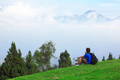 Man sitting on grass and looking mountain Stock Images