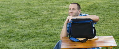 Man sitting on the grass outdoors. Man sitting on the grass outdoors gazing out while leaning on a cooler that is resting on a football shaped cutting board and Stock Photo