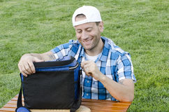 Man sitting on the grass. Man sitting on the grass outdoors with a smile on his face and wearing a backwards hat while zipping up a cooler that is resting on a Stock Images