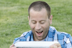 Man sitting on the grass outside in front of a table with a cooler. Man sitting on the grass outdoors with a very shocked and happy look on his face while Royalty Free Stock Image