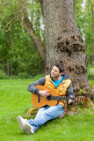 Man sitting on grass and playing guitar Stock Images