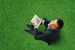Man sitting on grass with touch pad. Top view of smiley businessman sitting on the green grass and holding touch pad with growing graph Royalty Free Stock Images