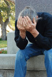 Man sitting at gravesite Stock Image