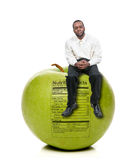 Man Sitting on Green Apple with Nutrition Label. A handsome young man sitting on a green apple with a nutrition label Stock Image