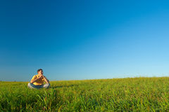 Man sitting on green field. Young man sitting on green field Stock Photo