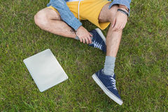 Man sitting on green grass with laptop near by. Cropped shot of man sitting on green grass with laptop near by Stock Image