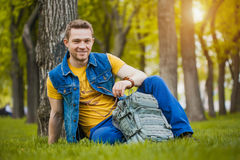 Man is sitting on the green grass in park Stock Photography