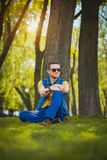 Man is sitting on the green grass in park Stock Images