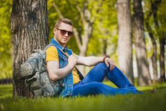 Man is sitting on the green grass in park Stock Photos