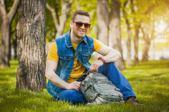 Man is sitting on the green grass in park Royalty Free Stock Photos