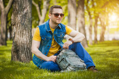 Man is sitting on the green grass in park Royalty Free Stock Photo