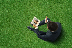 Man sitting on the green rgass Stock Photos