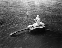 Man sitting on a guitar sailboat. (All persons depicted are no longer living and no estate exists. Supplier grants that there will be no model release issues royalty free stock photo