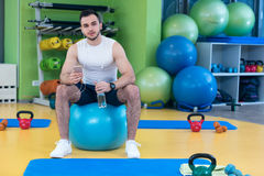 Man sitting on a gym ball holding a phone after doing a work out Stock Images