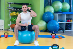 Man sitting on a gym ball holding a phone after doing a work out Royalty Free Stock Image