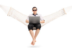 Man sitting on a hammock and working on laptop Royalty Free Stock Photos
