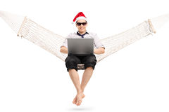 Man with sitting on hammock and working on laptop Stock Photo