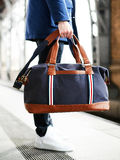 Man sitting hand holding camera and travel bag at the train station. stock images