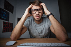 Man sitting with hands on head in front of computer Stock Photography