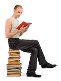 Man sitting on the heap of books Stock Photography
