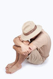 Man sitting hiding his face under a hat Stock Photography