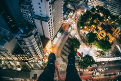 Man Sitting on High Rise Building Taking Photo Below Stock Image