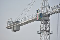 Man sitting high up in the sky in his crane Royalty Free Stock Images