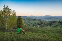 Man sitting on a hill above carpathian mountain village Royalty Free Stock Photography