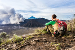 Man is sitting on the hill and looking on Bromo volcano eruption Stock Photos