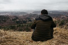 Man sitting on a hill looking at the horizon. stock image