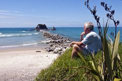 Man sitting on hill overlooking beach Stock Image