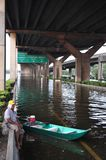 A man is sitting by his boat on the flooded highway in Bangkok, Thailand, in 31 October 2011 royalty free stock image