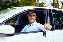 Man sitting in his car and holding keys royalty free stock images