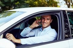 A man sitting in his car and talking on the phone stock photography