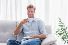 Man sitting on his couch drinking a coffee Royalty Free Stock Photos