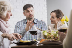 Man sitting with his family at the table Stock Photos