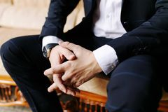 Man sitting with his hands crossed. Men`s hand in a blue suit, watch on the man`s hand, the hand of a businessman royalty free stock photo