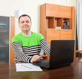 Man sitting at his laptop. Man sitting at computer in home interior stock photo