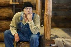 Man sitting in his log cabin thinking. Man in bib overalls sitting in his log cabin thinking about life Stock Photos