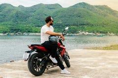 Man sitting on his motorbike, holding helmet on sea background