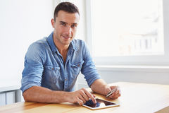 Man sitting in his office and using digital tablet royalty free stock images