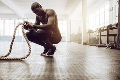 Crossfit guy training at the gym. Man sitting on his toes holding a pair of battle ropes for workout. Crossfit guy at the gym working out with fitness rope royalty free stock images