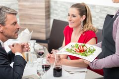 Man looking at food. Man sitting with his wife and looking at delicious food which is holding waitress in restaurant stock photos