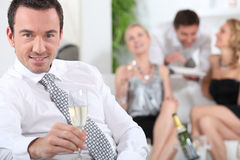 Man sitting holding champagne glass Stock Photo